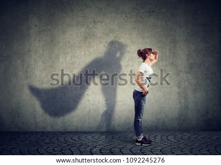 Side view of a woman imagining to be a super hero looking aspired.  Royalty-Free Stock Photo #1092245276