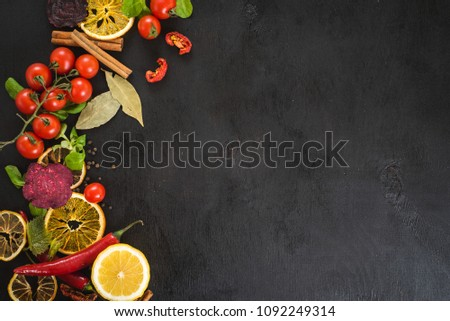 Fresh raw vegetables with different spices on black wooden background. Top view. Copy space. #1092249314