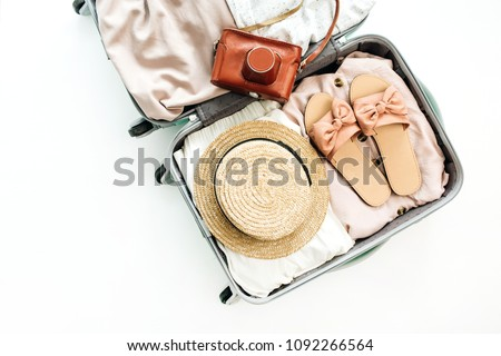 Hand luggage with stylish female straw, slippers and retro camera on white background. Flat lay, top view. Summer fashion clothes and travel concept. #1092266564
