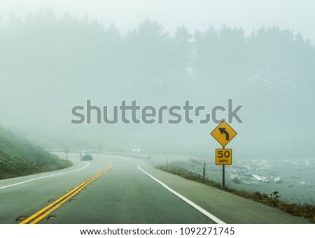 Fog Drifting Across a Highway with Green Trees in Background #1092271745