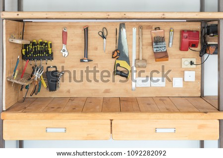 Wooden workbench at workshop. Lot of different tools for diy and repair works. Wood desk for product display. Copyspace. Labour day #1092282092