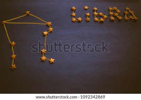 On a dark background, golden stars. The sign of Libra, the air element. Astrology, prediction by date of birth. Copy space, vignetting. The picture is made by the author.