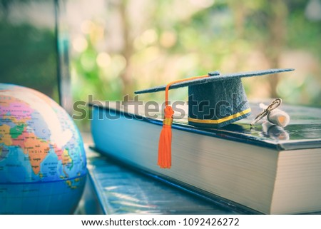 Graduate study abroad program for opening or expand world view concept Graduation cap or hat, world globe map and foreign book on a laptop, depicts an achievement or success in long distant learning Royalty-Free Stock Photo #1092426272