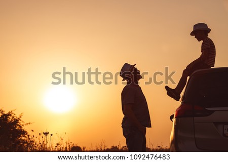 Father and son playing in the park at the sunset time. People having fun on the field. Concept of friendly family and of summer vacation. #1092476483