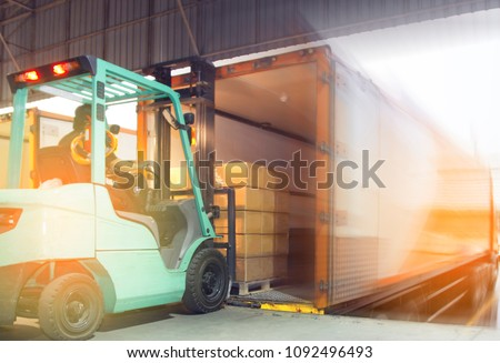 Freight transportation and Logistic warehouse, Forklift driver loading the shipment pallet into a truck container. #1092496493