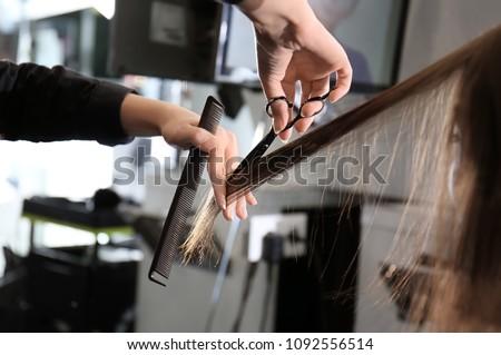Professional stylist cutting woman's hair in salon, closeup Royalty-Free Stock Photo #1092556514