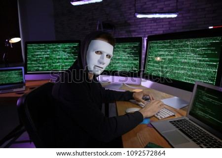 Masked hacker using computer in dark room. Threat of cyber attack #1092572864