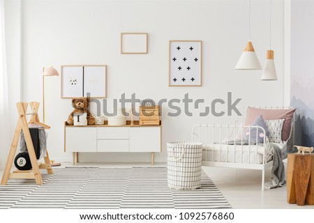 Natural, bright kid's bedroom interior with wooden furniture, designer accessories and posters on a white wall #1092576860