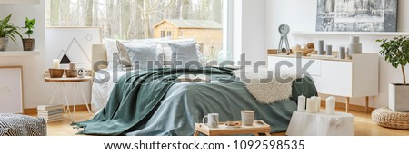 Green blanket on a cozy, double bed by a large window in a scandinavian style bedroom interior with a view at a forest Royalty-Free Stock Photo #1092598535