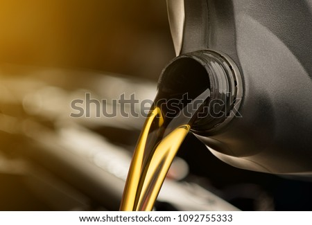 Pouring oil motor car  lubricant  from black bottle on engine background , service oil change auto repair shop  #1092755333