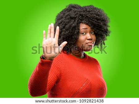 Beautiful african woman annoyed with bad attitude making stop sign with hand, saying no, expressing security, defense or restriction, maybe pushing