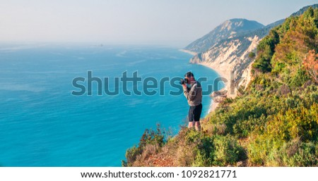 Photographer takes picture from the top of the cliff on west coast of Lefkada island, Greece, Europe. Spectacular morning seascape of Ionian Sea. Traveling concept background.  #1092821771