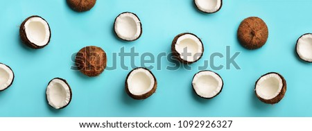 Pattern with ripe coconuts on blue background. Top View. Copy Space. Pop art design, creative summer concept. Banner. Half of coconut in minimal flat lay style #1092926327