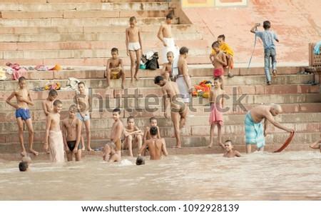 VARANASI, UTTAR PRADESH, INDIA - JULY 15 2007: Pilgrims bathing and performing ritual at the water holy Ganges river in the early morning #1092928139