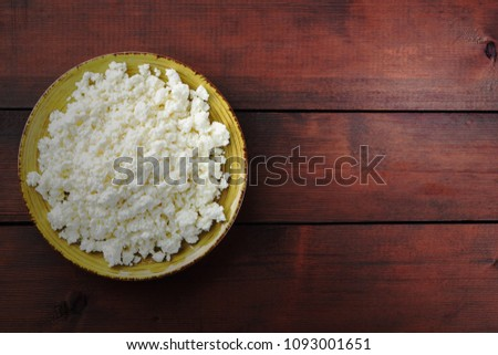 Cottage cheese on wooden boards, soft cheese on a yellow plate. Dairy product on a brown wooden background, healthy lifestyle. Copy space #1093001651