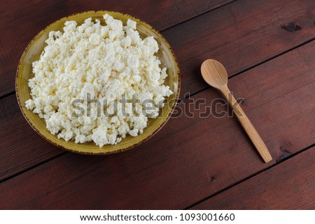 Cottage cheese on wooden boards, soft cheese on a yellow plate. Dairy product on a brown wooden background, healthy lifestyle. Copy space #1093001660