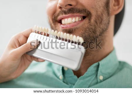medicine, dentistry and healthcare concept - close up of dentist with tooth color samples choosing shade for male patient teeth at dental clinic #1093014014