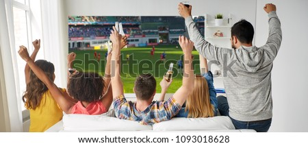 leisure, sport and people concept - happy friends with bottles of non-alcoholic beer watching soccer or football on projector screen at home #1093018628