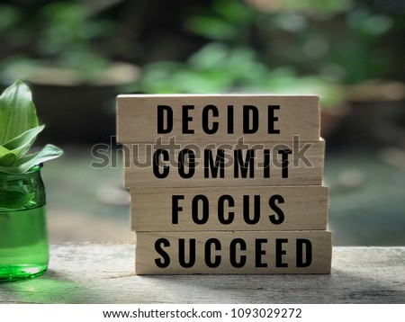 Motivational and inspirational quote - 'Decide, commit, focus, succeed' written on wooden blocks. With vintage styled background. #1093029272