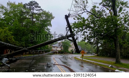 transformer on a electric poles and a tree laying across power lines over a road after Hurricane #1093124054