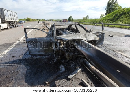 ODESSA, UKRAINE - May 17, 2018: accident on high-speed road. Car at high speed drove to road guard and burned. Terrible tragic accident due to speeding. Auto crashed into separating road safety guard #1093135238