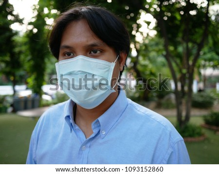 young asian man with protective mask in the park. #1093152860