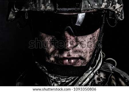 Cropped close up portrait of US special operations forces soldier, marine raider, modern combatant in helmet and glasses with dirty face after difficult military mission or battle looking at camera Royalty-Free Stock Photo #1093350806