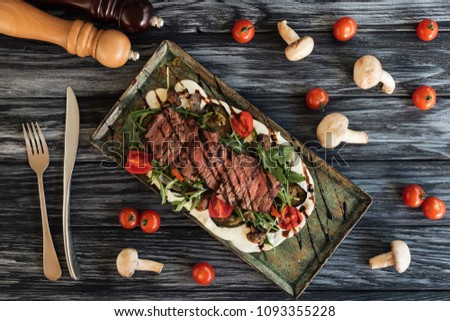 top view of delicious cooked steak with vegetables, fork with knife and spices on wooden table   #1093355228