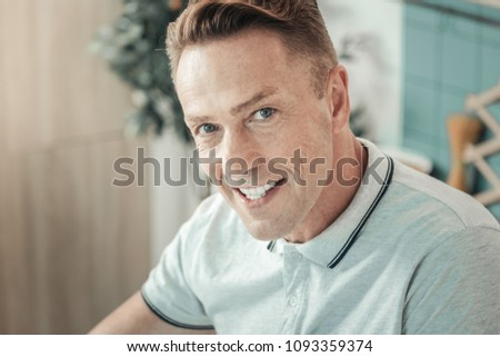 Pleasant smile. Handsome young man demonstrating his emotions and raising eyebrow while watching you #1093359374