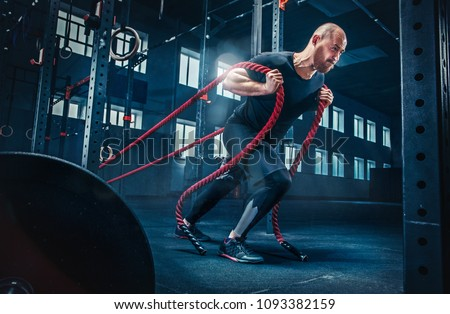 Men with battle rope battle ropes exercise in the fitness gym. CrossFit concept. #1093382159