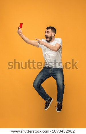 Protest - red card to the football referee. The young jumping man as football supporter with red card on orange background. Support concept. Human emotions, facial expression, soccer, football, sport #1093432982