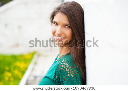 Closeup portrait of a happy young woman smiling, against a white brick wall, summer outdoors #1093469930
