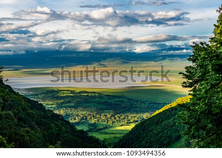 Elevated view of floor of Ngorongoro Crater from the southern edge of the crater.  Looking toward Lerai Forest and the alkaline crater lake, Lake Magadi, with clouds covering the rim on other side. #1093494356
