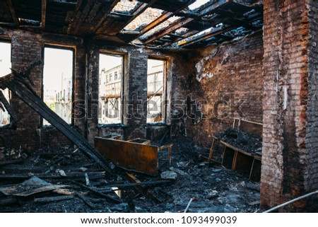 Ruins of burned brick house after fire disaster accident. Heaps of ash and arson, burnt furniture, collapsed roof, broken windows #1093499039