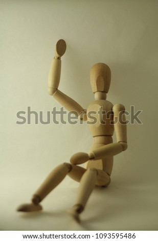 Sitting dummy moving right hand on white background with light from the right #1093595486