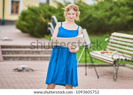 Beautiful girl-artist on the street in a blue dress draws a sketch of the picture  #1093605752