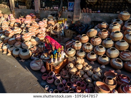 BIKANER, INDIA - March 4, 2018: Street Merchant Stores Selling Clay Ceramic Pottery Water Jugs at Dusk in Bikaner India #1093647857