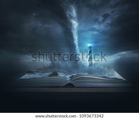 A big storm and tornado on top of the pages of a Bible with a bright lighthouse Royalty-Free Stock Photo #1093673342