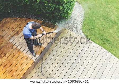 man cleaning terrace with a power washer - high water pressure cleaner on wooden terrace surface #1093680761