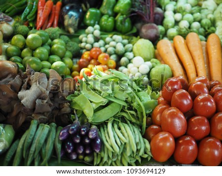 Variety of types and colors of fresh vegetables at a market in Thailand. Selective focus on Black Fungus (Jew's Ear Mushroom), Snow Peas (Sweet peas, Garden Pea) and Tomatoes. Healthy eating concept. #1093694129