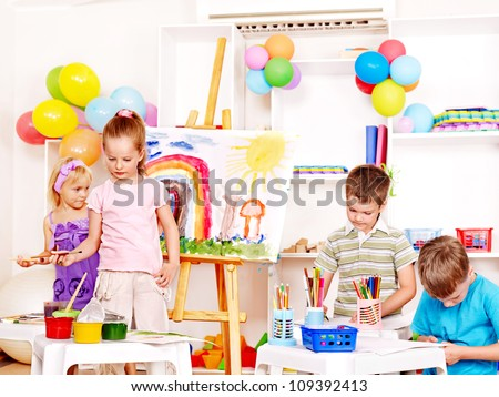 Group child painting at easel in school.