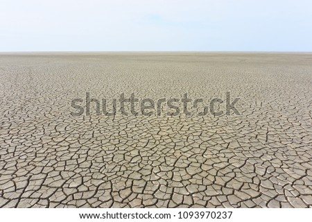Desolate landscape with cracked ground at the seashore. Brown, beige, light tan and grey colored. Concept of global warming. Royalty-Free Stock Photo #1093970237