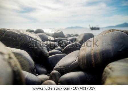 Beautiful black stone with boat on sea background on Koh Hin Ngam, Tarutao Marine National Park in Lipe Island, Satun Province, Thailand. Summer Concept. #1094017319