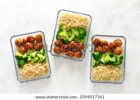 Asian style teriyaki sauce chicken meat balls with broccoli and rice prepared and put in a take away lunch boxes, view from above #1094017361