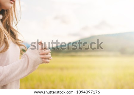 blurred photo,A young girl prayed for God's blessings with the power and holiness of God on the background of the morning sunrise over the golden meadow. God and Spiritual Concepts. #1094097176