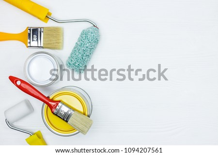white and yellow paint cans, brushes, paint rollers on white wooden desk surface flat view #1094207561