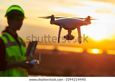 Drone inspection. Operator inspecting construction building site flying with drone. sunset #1094214440