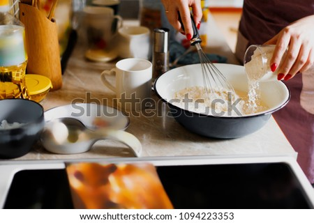 Mom prepares breakfast. A woman pours flour into a plate. The cooking process. Home kitchen. Sunlight #1094223353