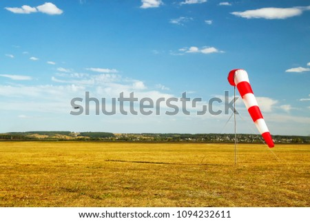 red and white windsock wind sock on blue sky, yellow field and clouds background #1094232611