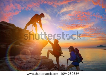Climbing team are on the climb to the cliff,hiking and team work concept.  Mountaineer climbing a steep cliff.                #1094280389